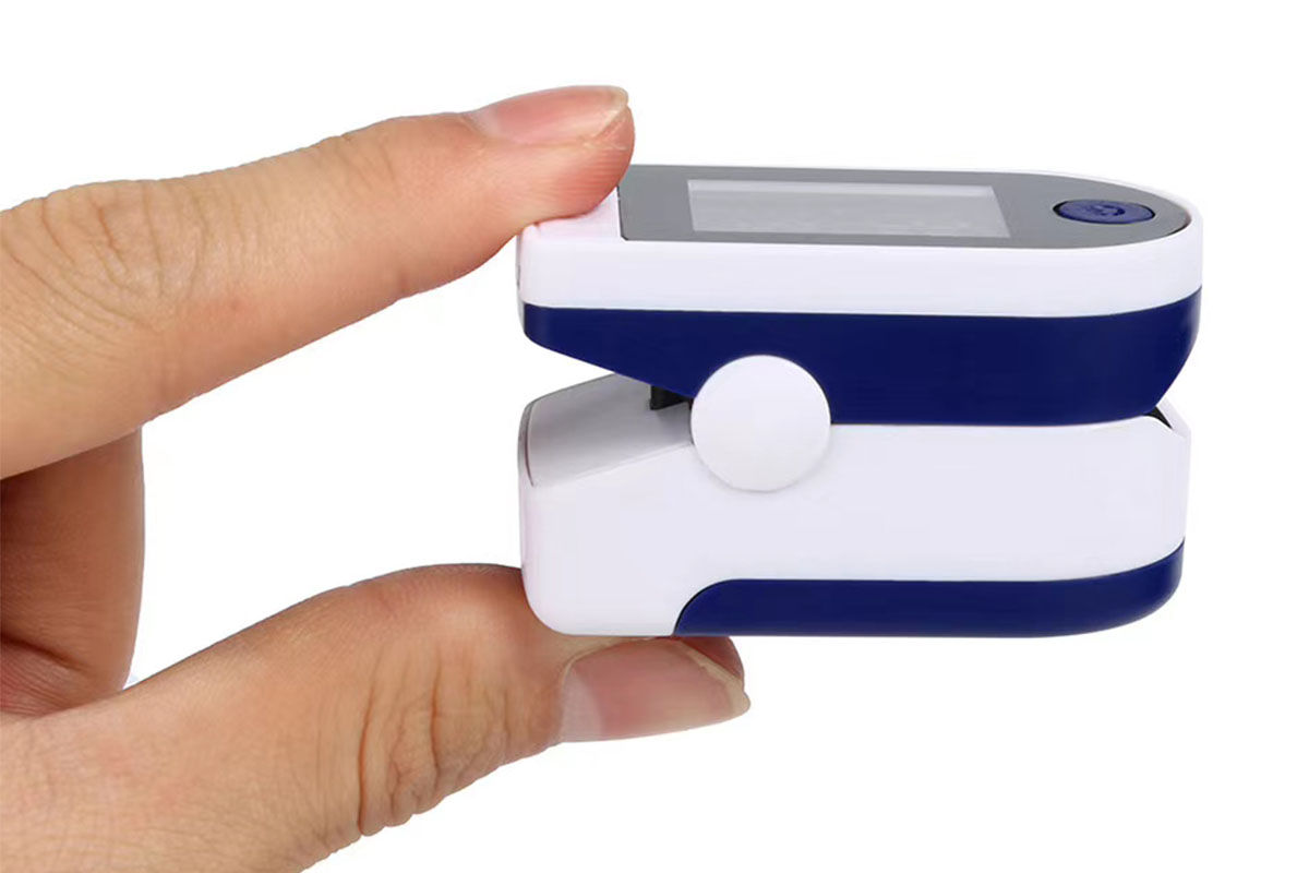 A person holding a fingertip pulse oximeter