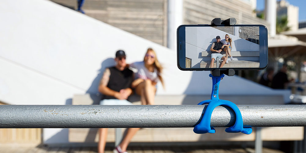 A tripod that has a flexible grip with a phone in the foreground, two people posing in the background