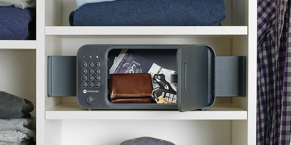 A safe on a shelf, filled with personal items such as a wallet, keys, and event tickets