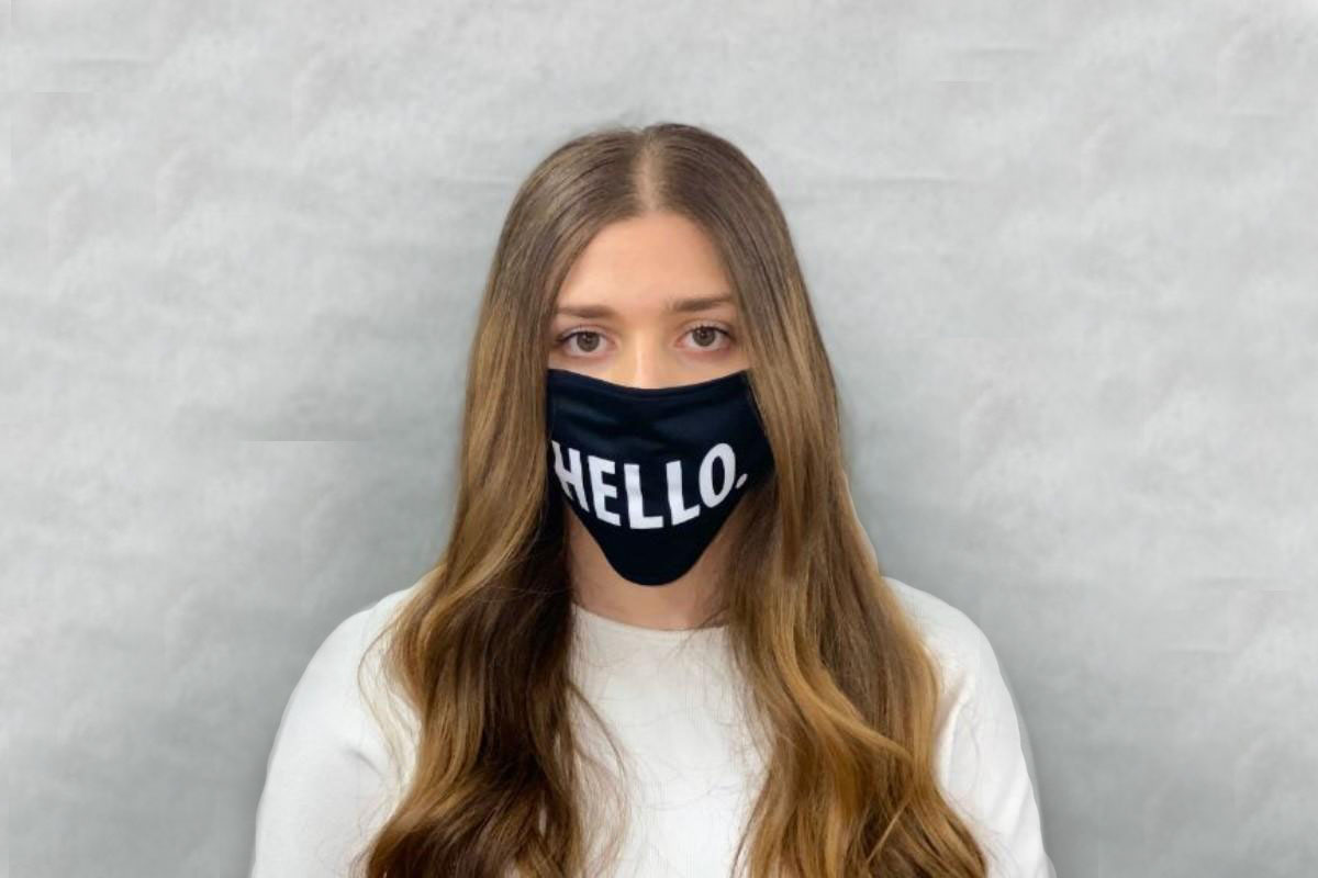 """A person wearing a face mask that says """"Hello."""""""