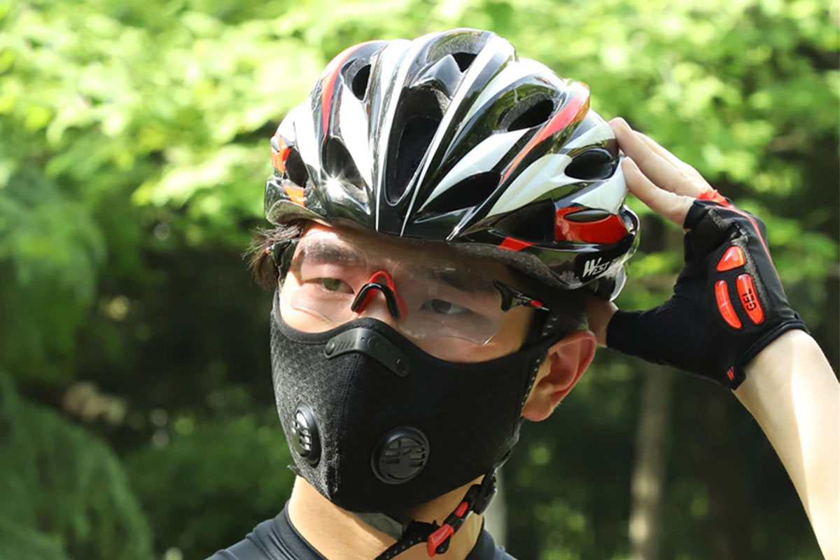 A person wearing a face mask, bike helmet, protective goggles and a bike glove.