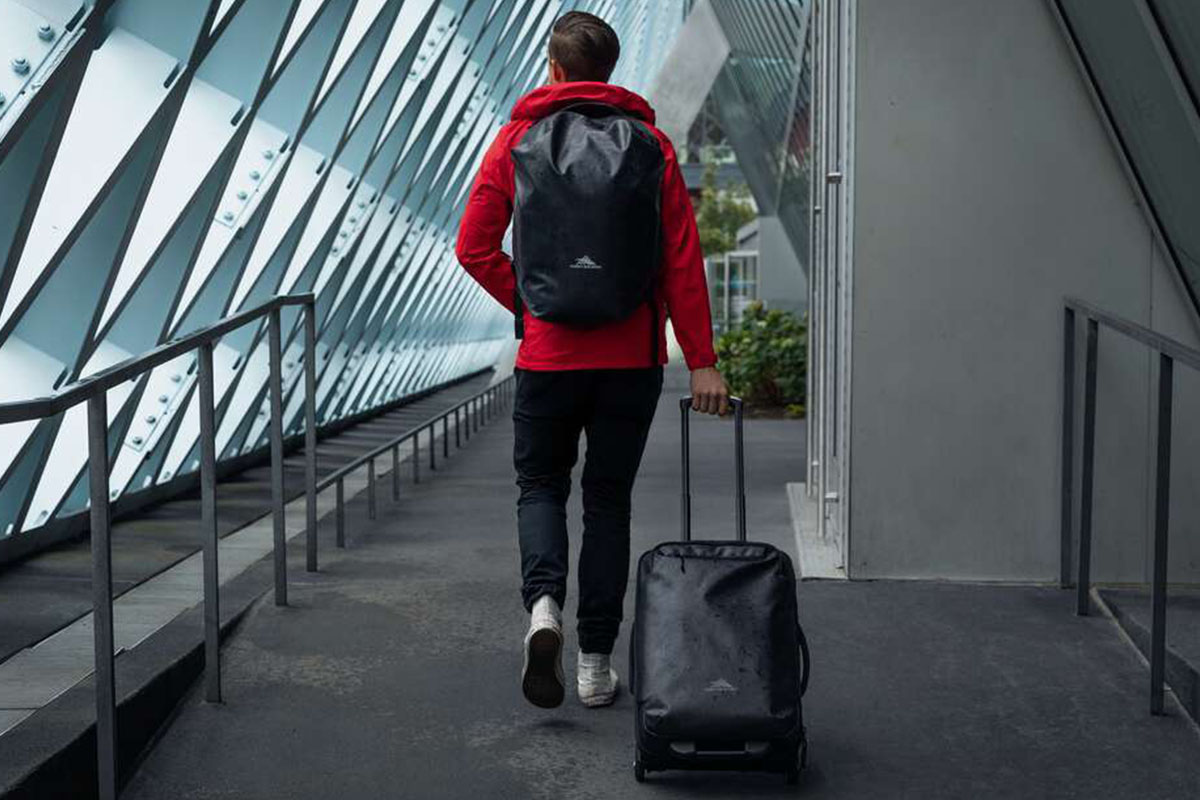 A traveller with rolling luggage and a backpack walking through a building.