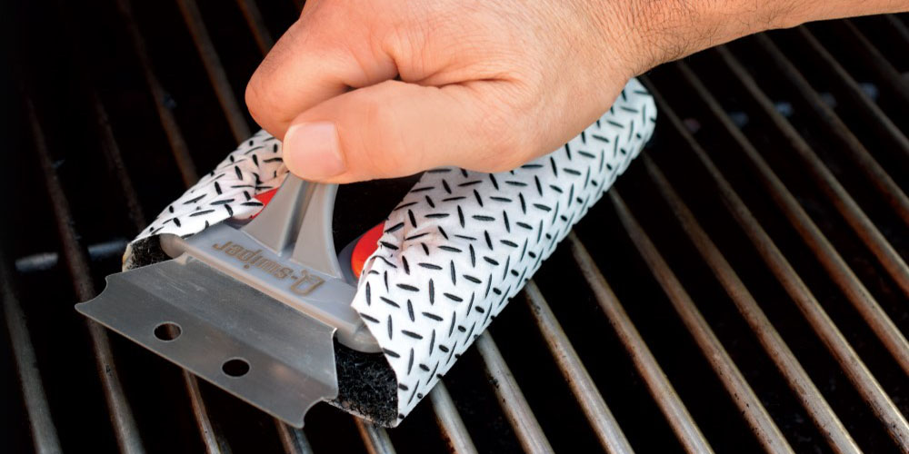 A person cleaning a grill