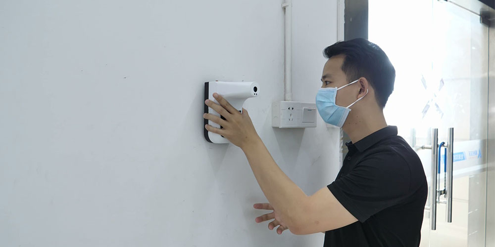 A person using a wall-mounted thermometer