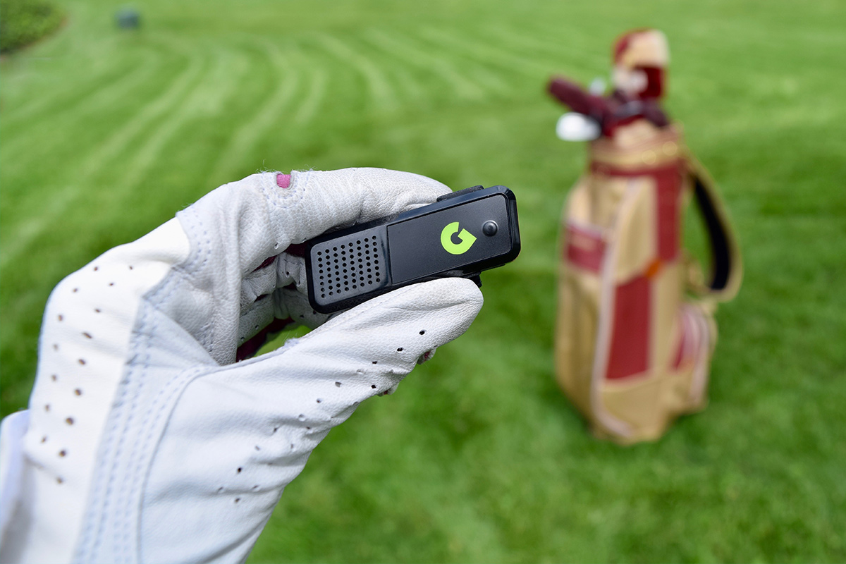 A person wearing a golf glove, holding a range finder.