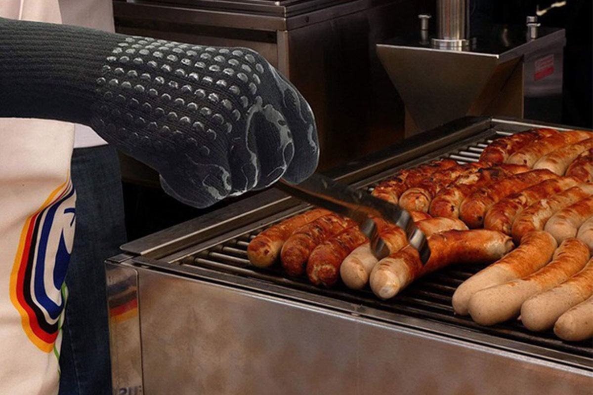 A person wearing a grill glove, cooking sausage on a grill