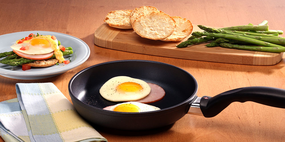 A wood countertop, with a nonstick pan with sunny side up eggs and ham inside, and other breakfast items plated nearby