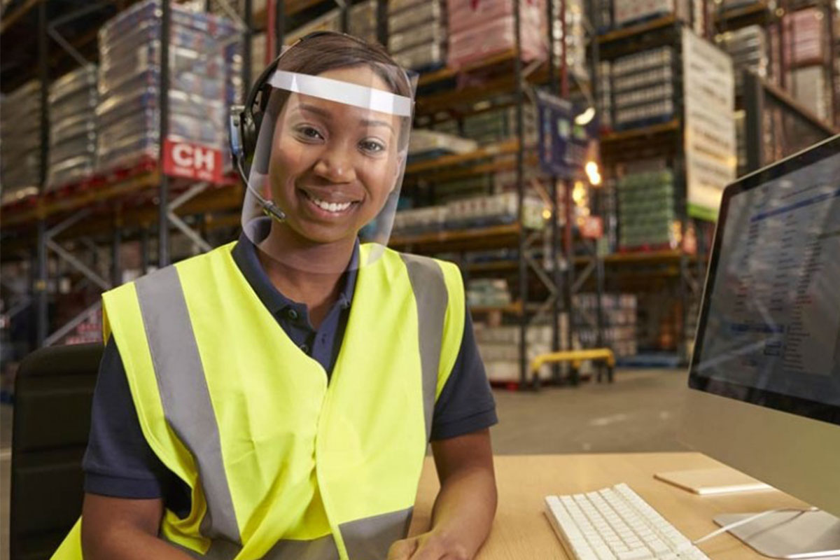 A person working in a large storage facility, working at a desk and wearing a face shield