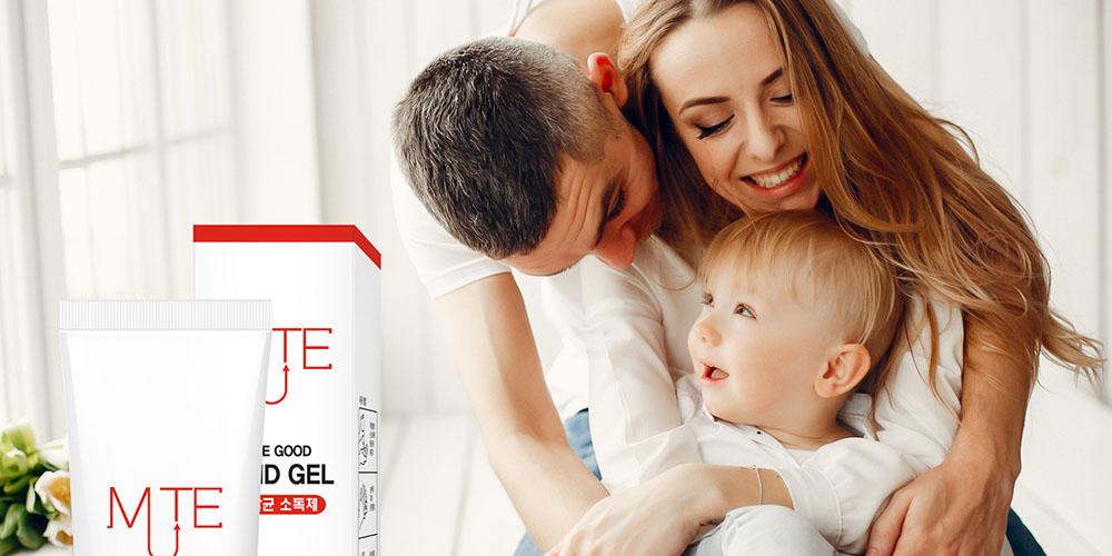 A family hugging near hand sanitizer