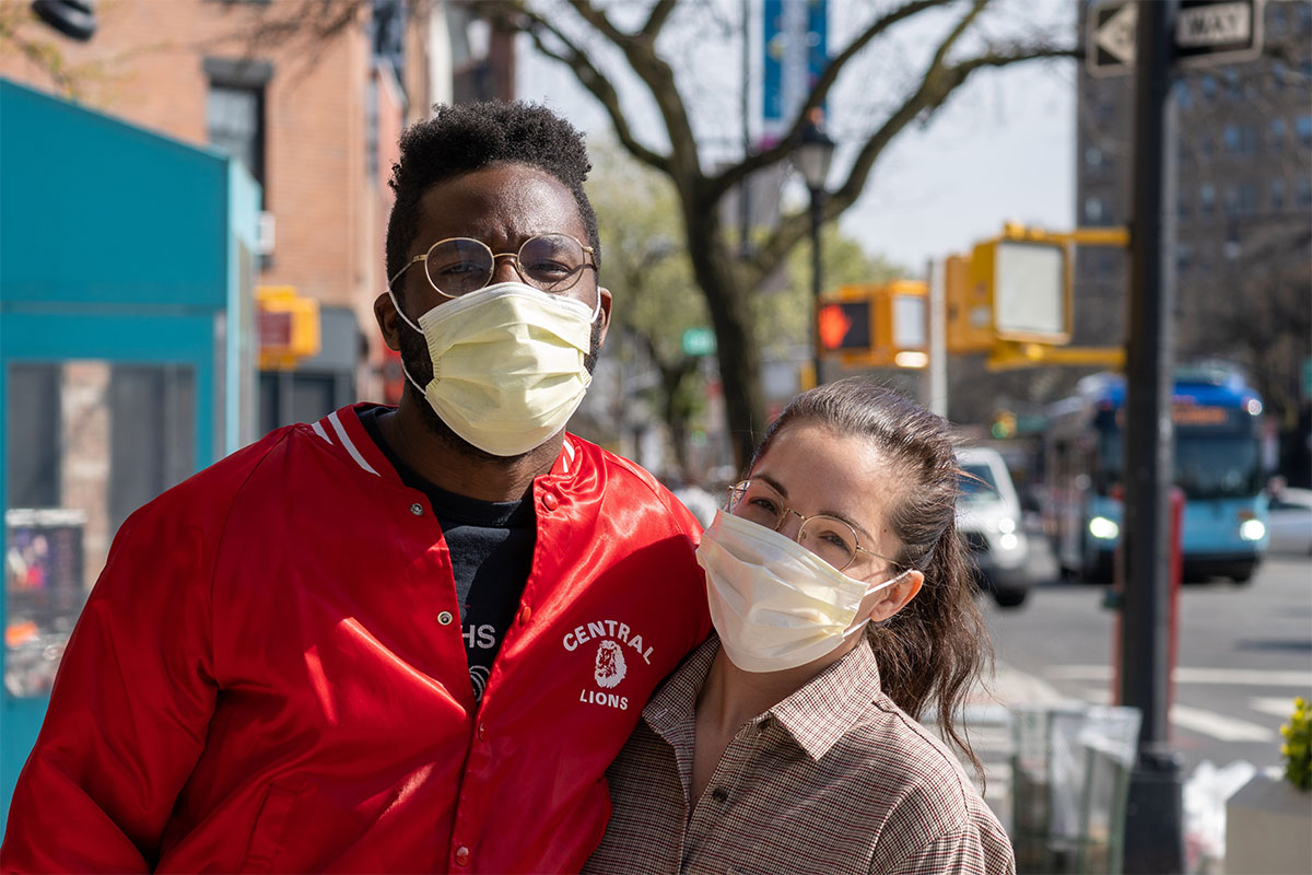 Two people outside wearing face masks