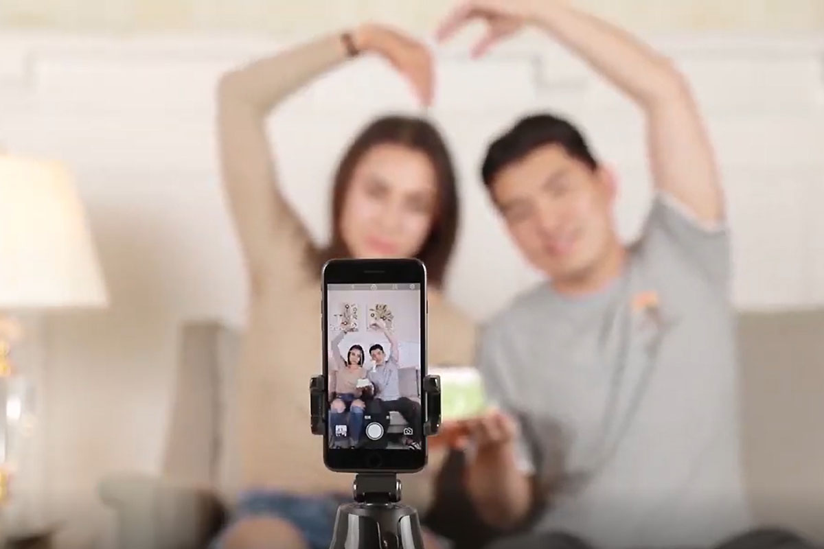 A selfie stick in the foreground, with a phone taking a photo of two people sitting on a couch with their arms making a heart shape