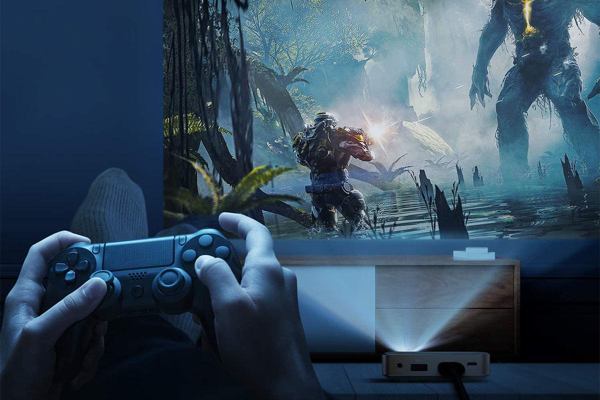 hands playing a video game on a controller, with a jungle scene video game projected on a wall