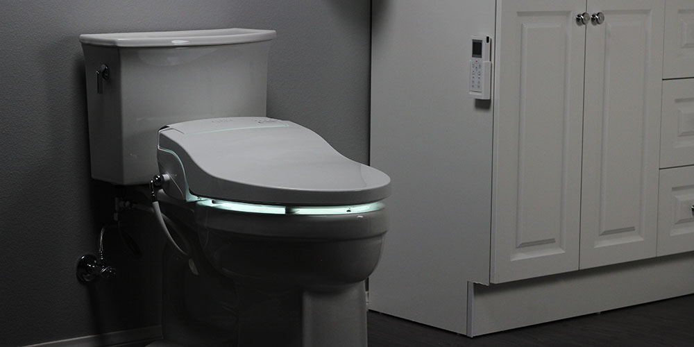 A toilet with a bidet attached, and a light up seat