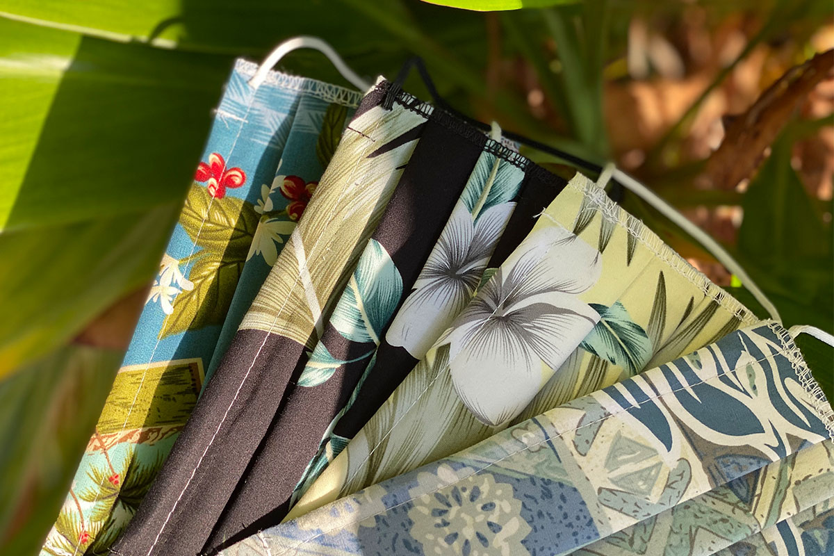 Four face masks with Hawaiian prints, fanned out on display against a plant.