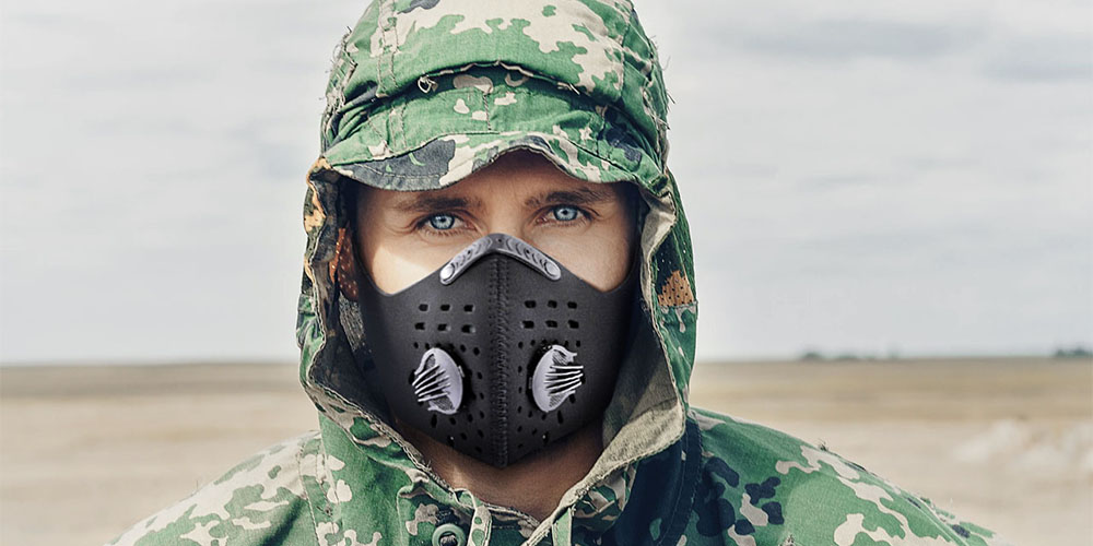 A person wearing a face mask, and a camouflage hooded jacket
